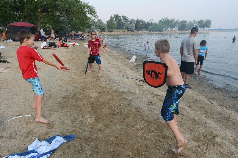 Kyle Bellisario, 10, left, Steven Bellisario, 12, and Kevin Binder, 8, have playful battle along the shore of Lake Loveland while playing together Wednesday, July 4, 2012.