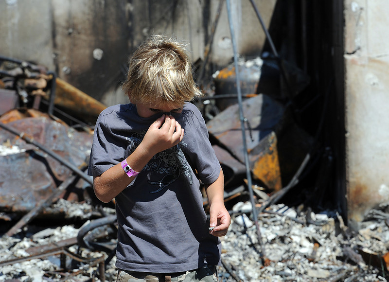 Hunter Squibb, 8, covers his nose while walking through the remains of his family's destroyed home in the High Park fire area.