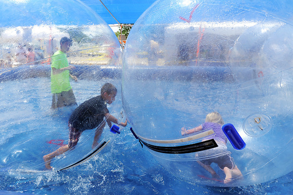 Emily Beck, 6, right, of North Platte, Neb. and Loveland resident Jacques Rodriguez, 7, splash around in the Water Bubbles attraction during the Loveland Loves BBQ, Bands and Brews event on Saturday, July 14, 2012.
