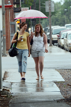 Kayla Sterner, left, and Kate Mattes share an umbrella as they walk together in downtown Loveland during an afternoon rainstorm after having coffee at the Coffee Tree.