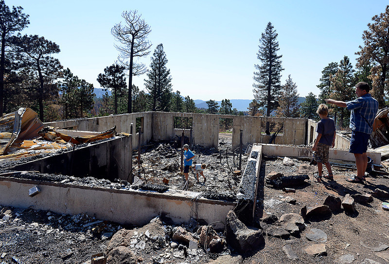 Mark Squibb, far right, and his children Dakota, 11, left, Tanner, 6, center, and Hunter, 8, look over the remains of their home that was destroyed in the High Park fire.