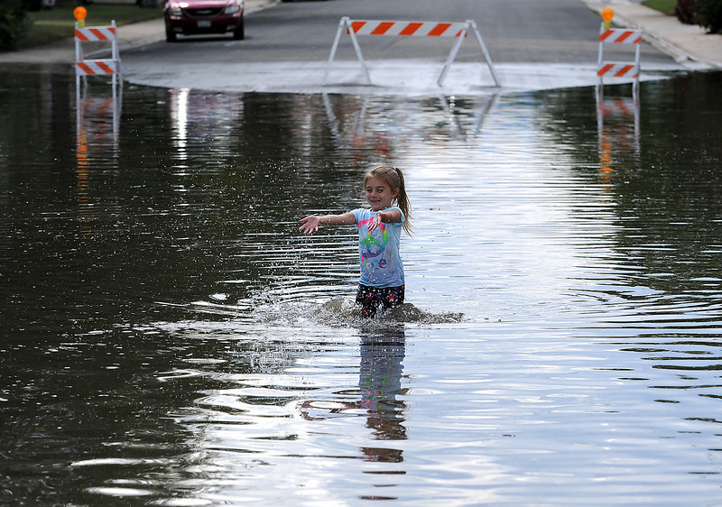 Hailey Zuniga, 4, splashes around in the water Wednesday at 16th Street SW between Elizabeth Ct. and Douglas Avenue when it flooded after a rainstorm. Barb Carr, who has live at that intersection for 20 years, said the area always floods after a heavy rainstorm.