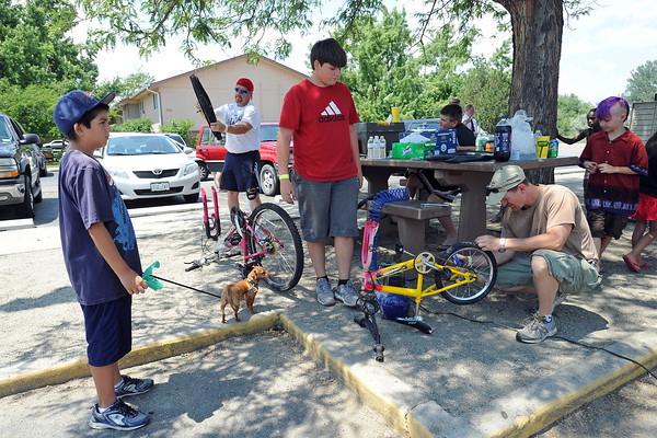 Karlos Vasquez, 11, left, holds onto his dog Lala's leash as he looks on while volunteers Bryan Johnson, back left, Owen Montgomery, 13, and Monty Eisenbraun repair bicycles at Maple Terrace Apartments on Thursday, July 12, 2012.