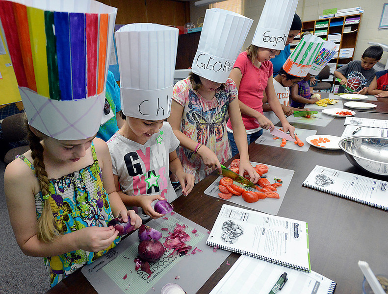 Haley Erickson, 8, left, and Chloe Domago, 8, center left, peel onions as Georgia Domago, 10 center, and Sophia Domago, 11, right, cut tomatoes and carrots Wednesday during a Cooking Matters cooking and nutrition class at Van Buren elementary School in Loveland.
