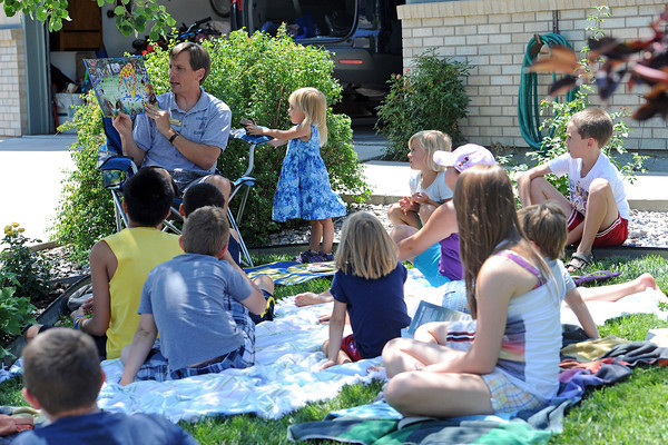 Stansberry Elementary School principal Grant Waller, back left, reads a book aloud to youngsters gathered at the Loveland home of one of his students during a summertime get-together Tuesday, July 10, 2012.
