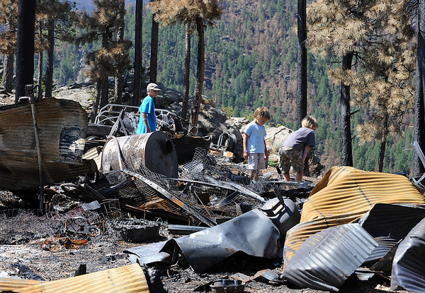 The Squibb boys, Dakota, 11, left, Tanner, 6, center, and Hunter, 8, walk through rubble on their property after their home was burned to the ground in the High Park fire.