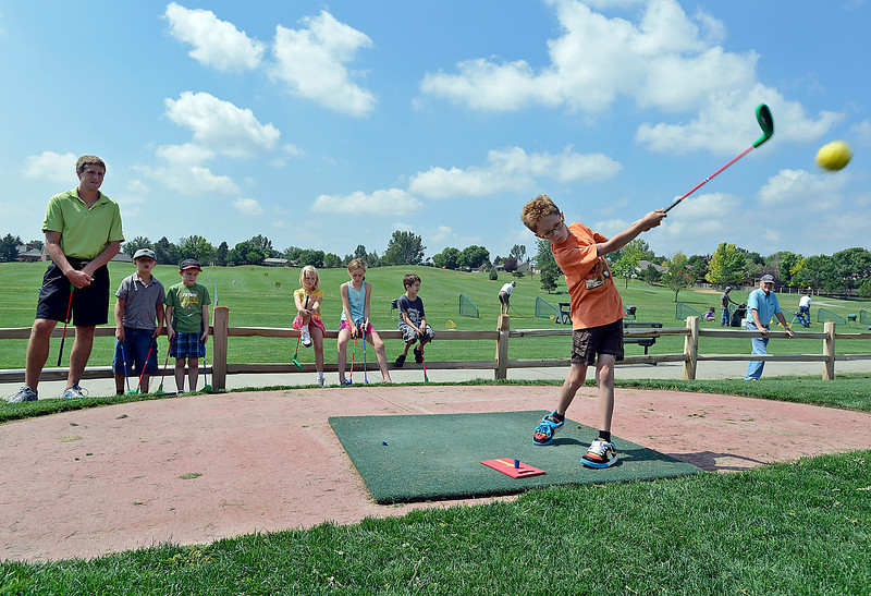 Gaius Buckley, 7, hits a tennis ball off the launchpad toward the green Tuesday while playing SNAG, Starting New at Golf, on the new course at Cattail Creek golf course in Loveland. He and other kids in the golf lesson program at the course got to try out the new course before it's grand opening which was hel Tuesday afternoon. The SNAG course, designed to make learning golf easy and fun, will be open daily starting today operating from 11:00 am until close.