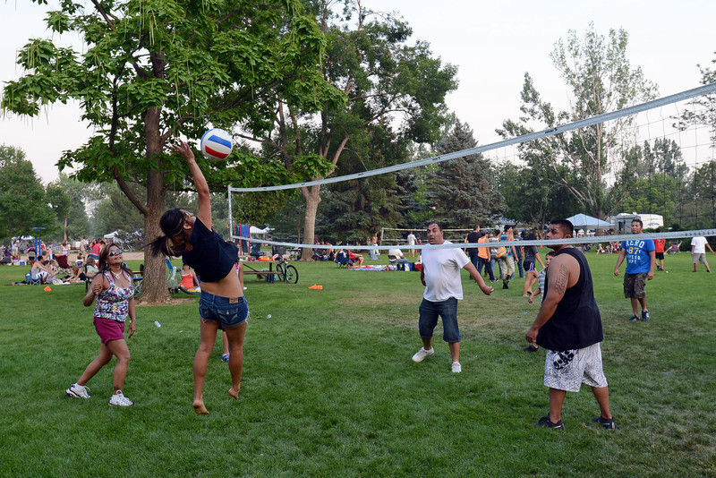 Annetta Maestas, left, looks on while Rubi Renteria leaps in the air to return a shot while playing volleyball with friends and family at North Lake Park on Wednesday, July 4, 2012.