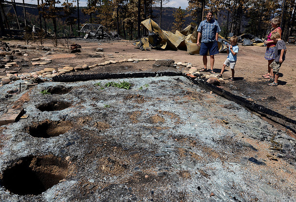 The Squibb family look at what is left of their greenhouse that was destroyed in the High Park fire.