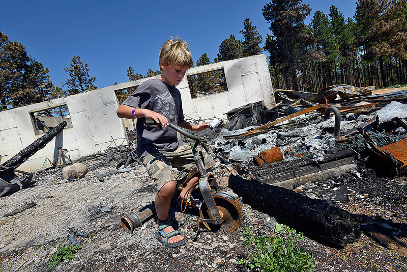 "Hunter Squibb, 8, sits on a charred tricycle while visiting the remains of his family's home that was destroyed in the High Park fire off Davis Ranch Road. His mother, Linda, looked at the burned tricycle and said ""All three of my boys rode on that tricycle."""