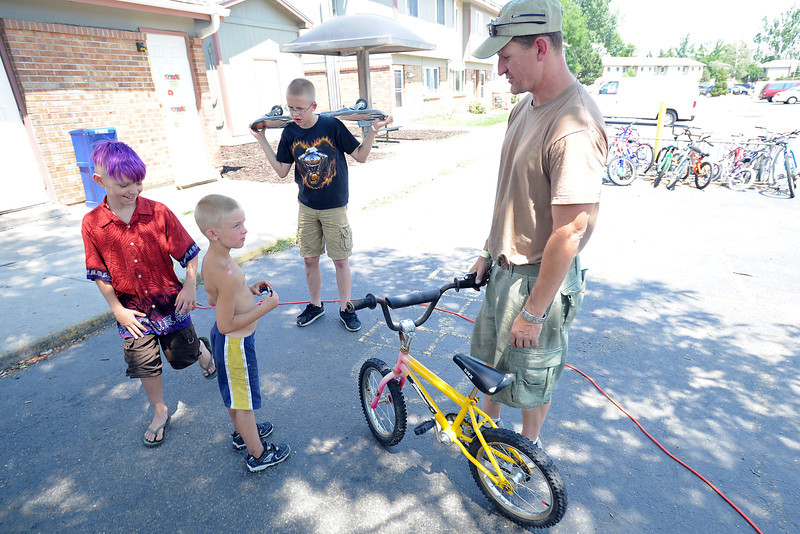 Patrick Constant, 9, left, Ryan Lewis, 6, and Wesley Palmer, 14, chat with volunteer Monty Eisenbraun who was repairing bicycles at Maple Terrace Apartments on Thursday, July 12, 2012.
