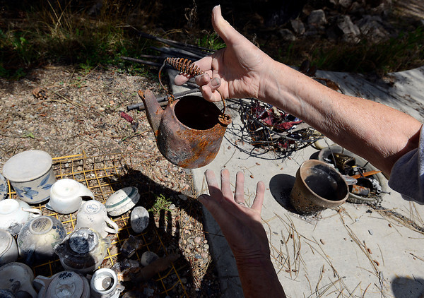 Patti Ellmann holds a metal teapot Monday found in the rubble that was left after her home burned in the High Park fire. Below are antique items given to her by her mother-in-law. She found the teapot on a hike with her parents when she was a child so she was thrilled to find it had survived the fire.