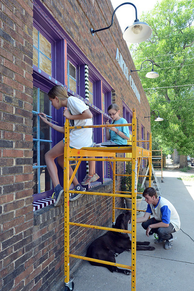 Cory Wolf, 17, right, pets a dog named Henry while taking a break from working with Brooke Preusse, 12, left, and Delaney Lord, 11, as they decorate the outside of the the Wildfire Community Arts Center at 425 Massachusetts Ave. in Berthoud on Thursday, July 26, 2012.