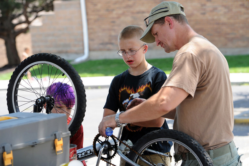 Patrick Constant, 9, left, and Wesley Palmer, 14, watch as volunteer Monty Eisenbraun performs maintenance on a bicycle at Maple Terrace Apartments on Thursday, July 12, 2012.