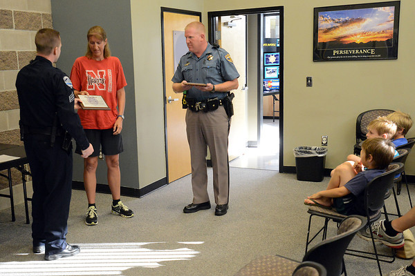 Loveland Police Sgt. Ryan Ertman, left, presents plaques to Cherie Circenis and Colorado State Patrol trooper Scott Pucket during a Life Saving Award ceremony at the CSP's Larimer County Troop office on Wednesday, July 25, 2012.