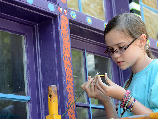 Loveland resident Delaney Lord, 11, adds glue to the back of a fake gemstone before placing it on the outside of the Wildfire Community Arts Center in Berthoud while decorating the building Thursday, July 26, 2012 with its design inspired by the look of Pakistani taxi cabs.