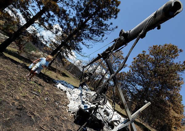 Tanner Squibb, 6, checks out his family's sailboat that was destroyed in the High Park fire.