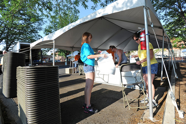Tera Robben, right, and her daughter Holly Leppert with Robin Event Rental hang signs inside a tent while setting up for the Loveland Loves BBQ, Bands and Brews event in downtown Loveland on Thursday, July 12, 2012.