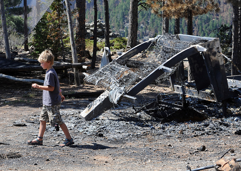 Hunter Squibb, 8, walks near the shell of a camper that was destroyed along with his family home in the High Park fire.