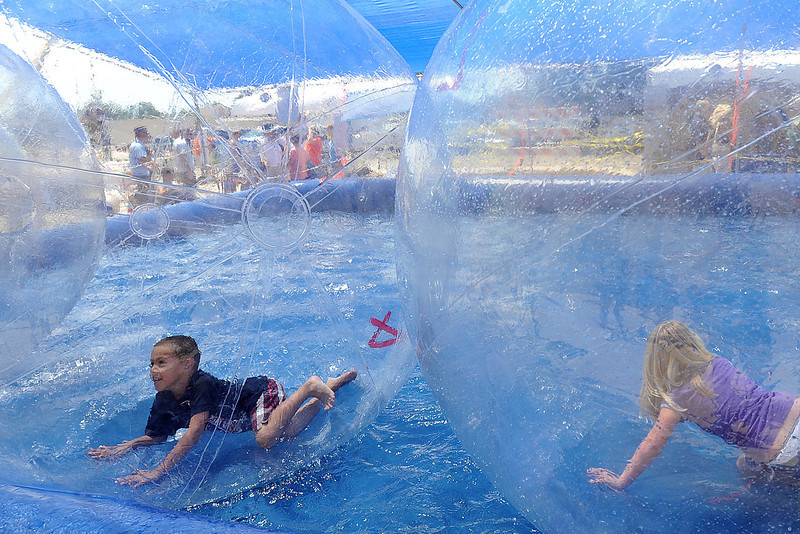 Loveland resident Jacques Rodriguez, 7, left, and Emily Beck, 6, of North Platte, Neb. splash around in the Water Bubbles attraction during the Loveland Loves BBQ, Bands and Brews event on Saturday, July 14, 2012.