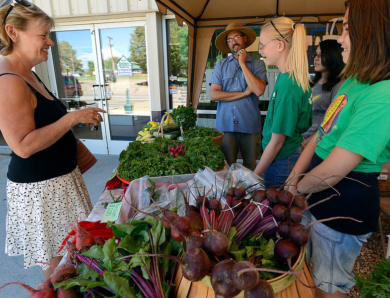 "Eco Possums members talk about the variety of fresh vegetables they have for sale to customer Sally Buonpane, left, Thursday at the Youth Farmers Market run by Eco Possum members located in front of the Habitat for Humanity Restore in Loveland. From left the Eco Possum mebers are Emme Janssen, 12, Allie Wilson, 13, and Maya Bontrager, 11. Garth Bontrager, Community Garden coordinator, center, also talks about the produce available. While commenting about how beautiful the farmer's market was Buonpane said ""I feel like I'm in the wine country in California."""