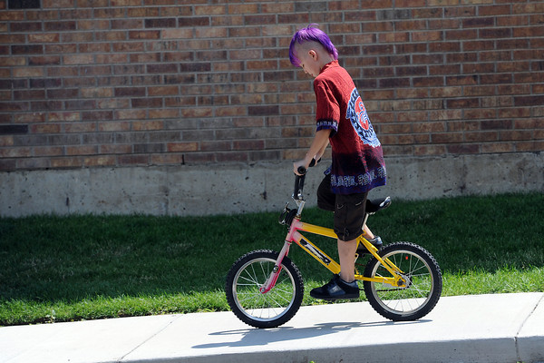 "Patrick Constant, 9, takes his bicycle for a spin after getting it repaired by members of the ""Week of Hope"" volunteer group at Maple Terrace Apartments on Thursday, July 12, 2012."