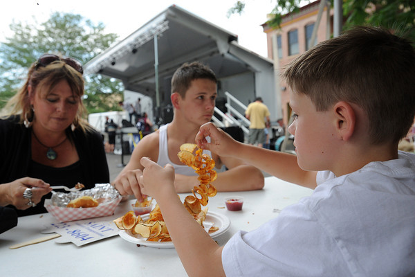 Shawn McNeill, 9, right, enjoys a snack with his mother Debby McNeill and brother Brandon McNeill, 14, while listening to live music during the Loveland Loves BBQ, Bands and Brews event on Saturday, July 14, 2012.