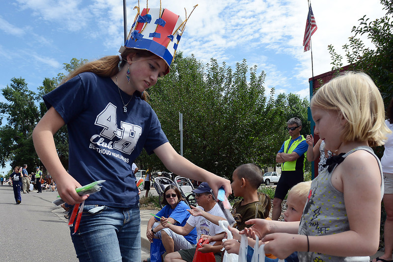 Brenna Conlon, 14, left, hands out frozen treats to parade watchers along the route for the Larimer County Fair Parade on Saturday, July 28, 2012 in downtown Loveland.