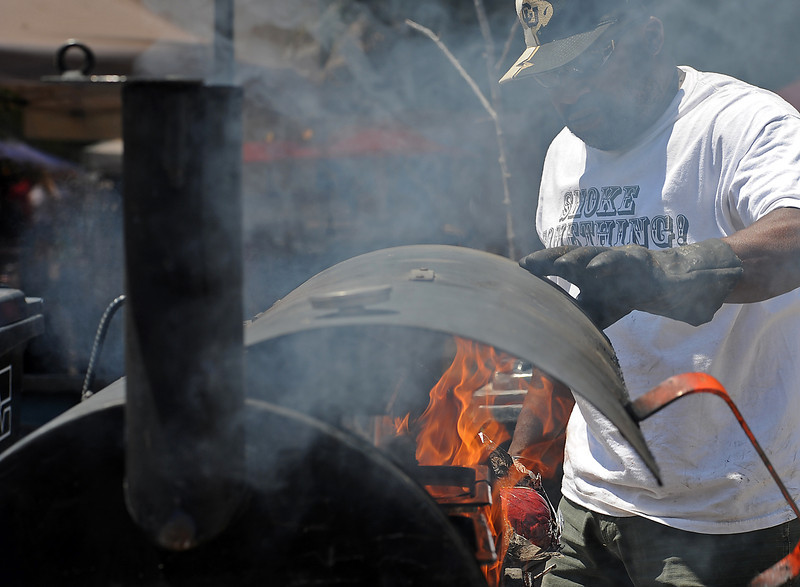 "Darryl ""Rat"" Johnson closes his smoker after checking on some beef brisket and pork shoulder at the Rat's Woodshack booth Friday during Loveland Loves BBQ, Bands and Brews in downtown Loveland."
