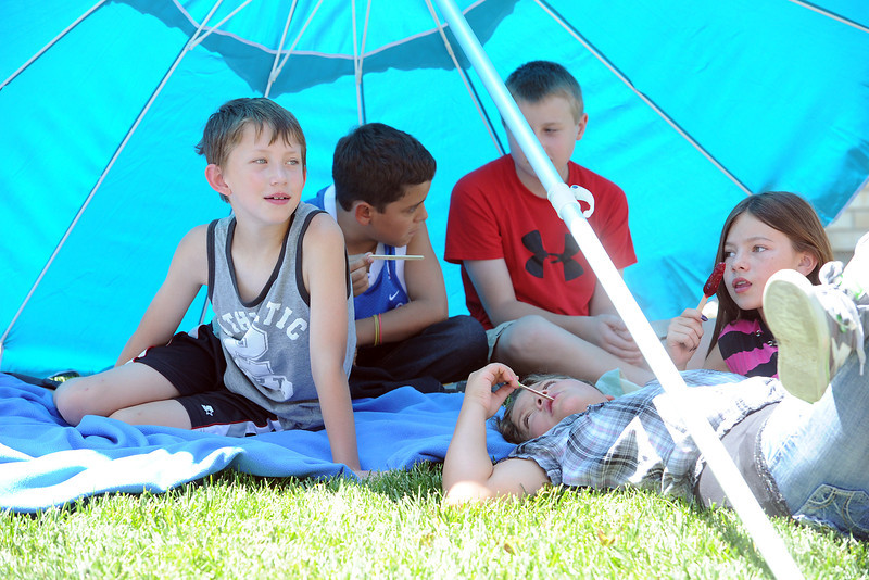 Youngsters hang out on the grass under a giant umbrella while eating frozen treats and listening to a story being read by Stansberry Elementary School principal Grant Waaler during a get-together Tuesday, July 10, 2012. From left to right are Shane Meese, 11, Isaiah Hildebrand, 10, Devon Evert, 10, Micaiah Hildebrand, 10, and Shelby Olson, 10.