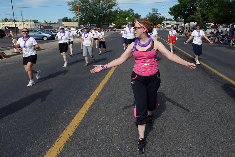Cindy Lewis, front, walks along the parade route with others in the Curves Circuit with Zumba entry during the Larimer County Fair Parade on Saturday morning in downtown Loveland.