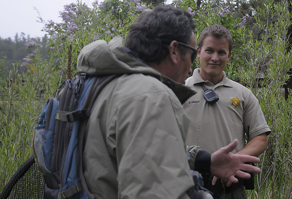Reporter-Herald/ Chad Spangler<br /> Larimer County Open Space Ranger Steve Gibson chats with a fisherman after checking his license on the Thompson River on Saturday afternoon. One of Gibson's many responsibilities is insuring that visitors fishing in the county open spaces have proper licenses.
