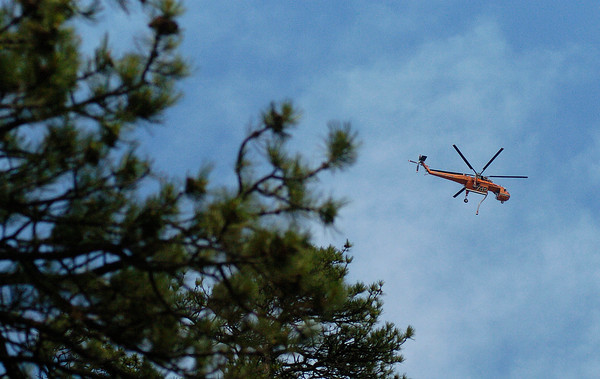 A helicopter returns from a drop near the Round Mountain fire on Sunday. Air drops were performed on the Cow Creek fire in Rocky Mountain National Park but the rain of the previous day helped firefighters get a handle on the Round Mountain fire.
