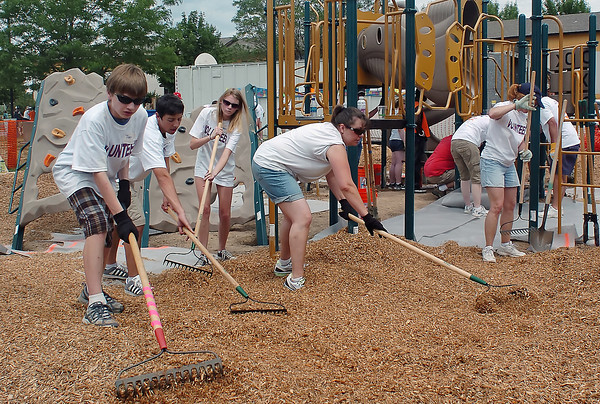 Volunteers spread mulch around newly-installed playground equipment Saturday at Orchard Place Apartment Community while making a variety of improvements to the area. From left are Trent Gamber, 13, Wade Griffis, 18, Alyssa Sanderson, 15, Tammy Morgan and Cindy Feneis.