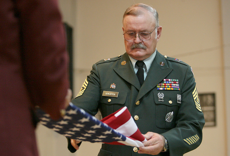 1st Sgt. retired, Ron Schlatter, demonstrates the correct way to fold an American Flag while Dennis Epp, chairman of the board of trustees in the Elk's Club holds the other end of the flag Sunday during a flag retiring ceremony at the Loveland Ek's Lodge