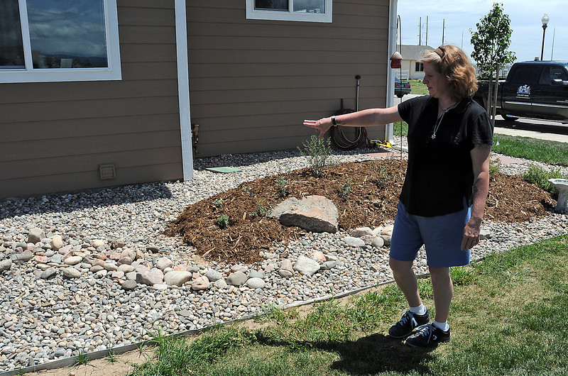 Deserie Newton speaks about the rocks and plants that were designed and installed by employees from Empire Landscaping at her new home in Loveland that was built by Habitat for Humanity.
