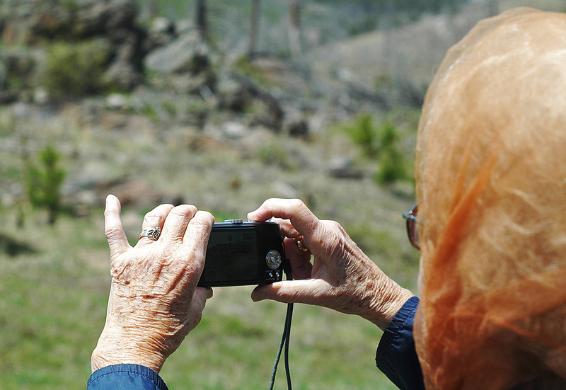 Lorna Miller snaps a photo of her property that was damaged by the Bobcat Gulch Fire in June, 2000.