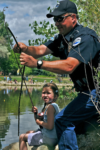 Officer Dave Sloat helps his neice, Andy Newby, 6, untangle her line, Saturday, after catching a stick with her bluegill during The Loveland Police Department Fishing Derby at North Lake.