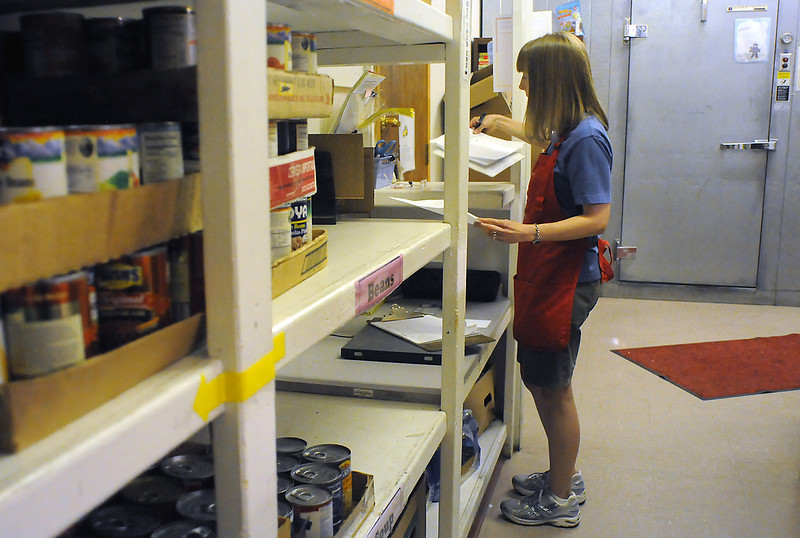 Erin Becerra, food program manager for House of Neighborly Service, catalogs incoming food donations Thursday in the food room of the downtown Loveland organization.