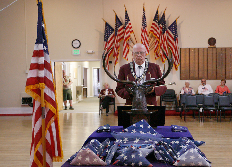 Dennis Epp, chairman of the board of trustees, brings a flag that will be retired to the center of the room Sunday during a flag retiring ceremony at the Loveland Elk's Lodge.