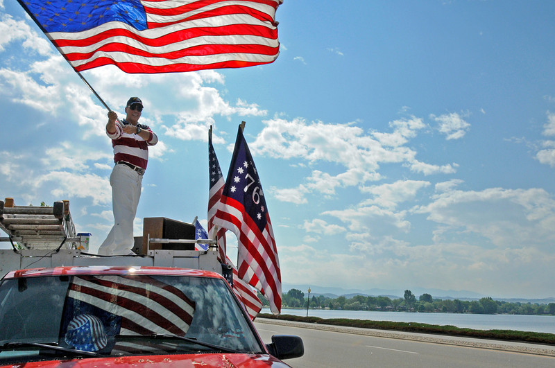 Loveland resident Dave Cook waves an American flag to passing cars in celebration of Flag Day near Lake Loveland. Cook was joined by dosens of members from the Loveland 912 Project, who organized the event.