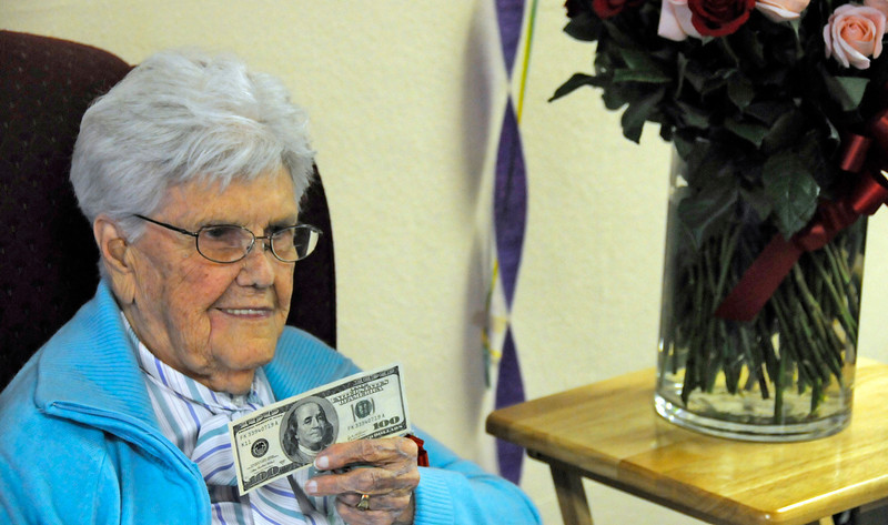 Loveland resident Myrtle Lyon holds up the 100 dollar bill she received during her 100th birthday party with friends and family at Silver Leaf Apartments on Wednesday. She moved to Loveland in 1994 to be closer to her family, which today consist of four children, 14 grandchildren and 17 great-grandchildren. She enjoys doing word puzzles, and drinks three Pepsis a week.