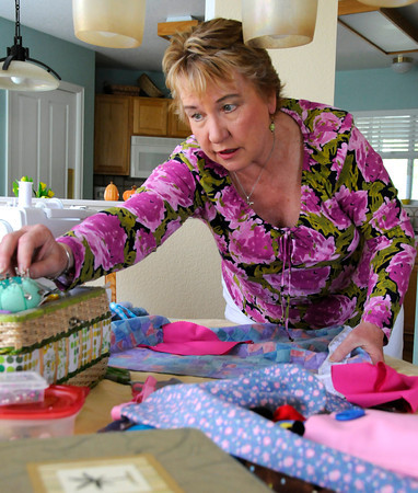 Loveland resident Carolyn Griebe reaches for a pin to attach lace to a dress made from a pillowcase on Monday. The dresses will help clothe poor children around the world.