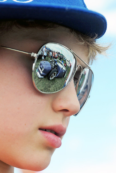 A car is reflected in Loveland resident Caden Denton's sunglasses as he checks out the cars on display Saturday during the Goodguys Colorado Nationals at The Ranch.