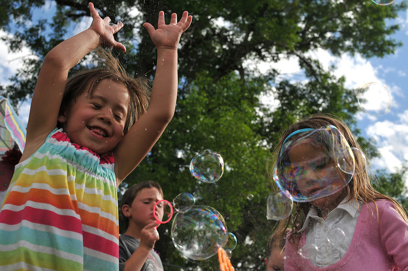 Left to right, Ally Miramontes, Branden Flores, and Ashton Balentine play with bubbles, Saturaday, Jun 5, during the 56th annual Berthoud Day along Mountain Ave.