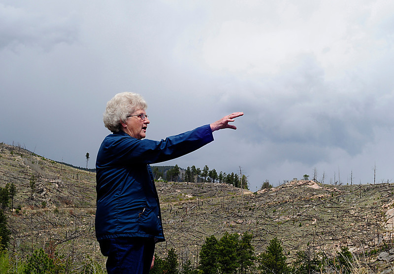 Reporter-Herald/ Chad Spangler<br /> Loveland resident Lorna Miller points out damage caused by the Bobcat Gulch Wildfire outside of Drake. Miller and her husband, not pictured,  lost a family cottage as a result of the fire.
