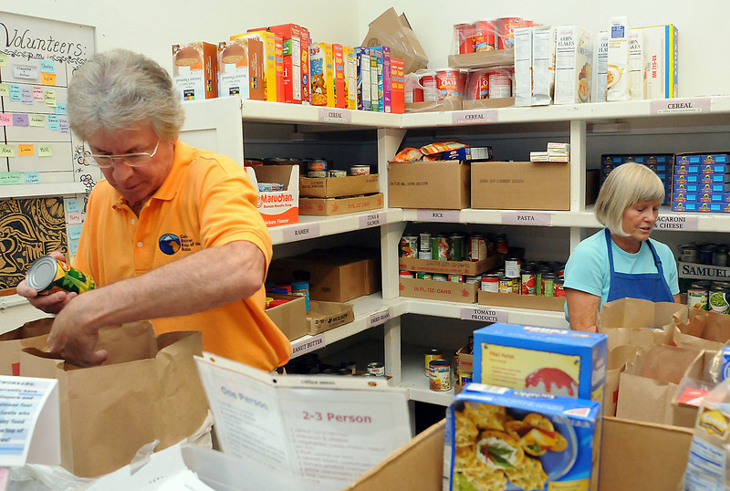 House of Neighborly Service volunteers Bill Hordinski, left, and Deb Weiszmann sort and package food items Thursday for pickup by needy individuals and families at the downtown Loveland facility.