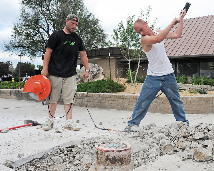 Employees from Scott A. Babb & Assoc. work on a landscape renovation project Friday afternoon in the 100-block of East 7th Street at Key Bank. Duztin Speltz, right, swings a sledge hammer to break up concrete while he and Ryan Hays prepare to lower a utility access so that it's level with the surrounding sidewalk.