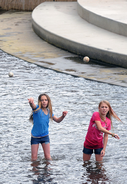 Loveland resident Destiny Pritchard, 10, left, and Savannah Guzzy, 11, of Arizona and stand in the wading area at Fairgrounds Park as they throw baseballs upstream to catch as they float back down while playing together Tuesday at the park.