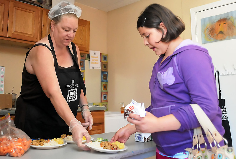 Ten-year-old Odalys Pastrana picks up her lunch from volunteer Janice Hinds on Thursday at the Maple Terrace Kids Club as part of the Kids Cafe lunch program.